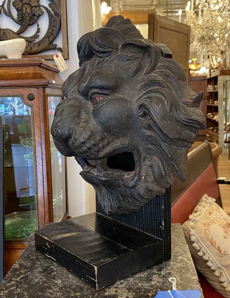 Great looking 1890s antique cast iron lion head mounted on a painted black wooden stand. Head features a nice blackened patina. This can be seen at our 333 West 52nd St location in the Theater District West of Manhattan.
