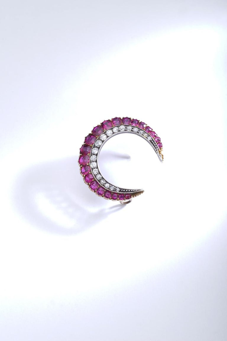 Crescent Ruby Diamond Brooch.  Silver and pink gold. Crescent brooch, set with cushion-shaped and round rubies. Circa 1890.  Diameter approximately 1.18 inch.