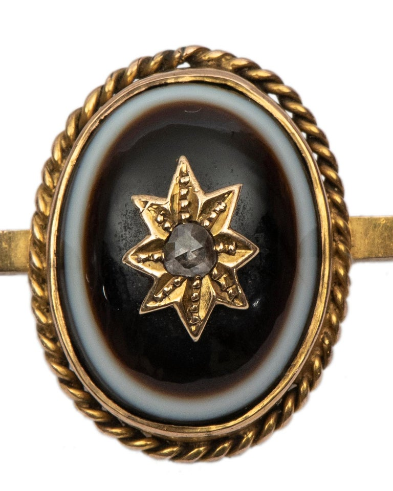 This late Victorian bar pin is set with an oval bull's eye banded agate centered by a rose-cut diamond on a gold star motif, within a twisted ropework border.  -2 1/4 in (5.5 cm) long, oval bezel: 3/4 in. (2 cm) long   Circa 1890, stamped 9ct