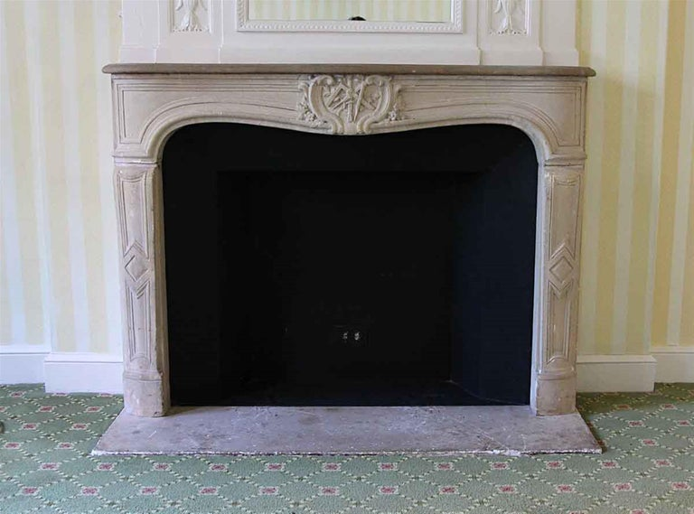 1890s French made Louis XV carved limestone mantel with a replacement shelf. This mantel was imported from Europe and installed in the NYC Waldorf Astoria Hotel of Park Avenue, New York City in 1931. There is minor chipping which appears somewhat