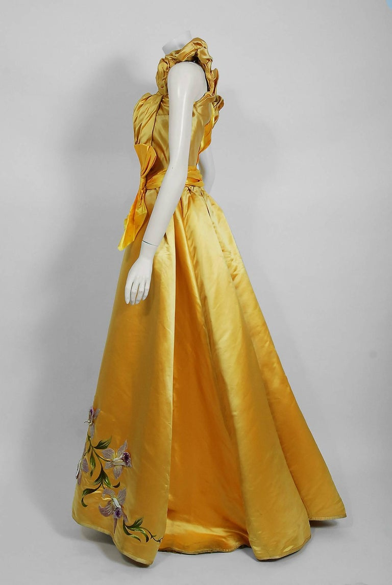 Undiminished by time, this 1895 Mme Arnaud on 16 Rue Bassano Paris couture ensemble still casts its seductive spell. An exceptional Victorian evening ensemble fashioned from vibrant sunshine yellow silk-satin. The gorgeous three-dimensional purple