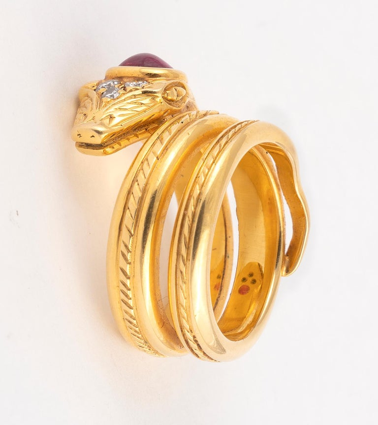 the triple coil gold band broadening at the head, this inset with cabochon cut ruby and three diamonds. Width across bands (at rhe head) 1.5cm / 5/8'' Weight: 16g Size : 6
