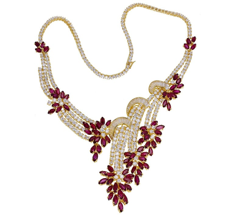An astonishing, exceptional quality ruby and diamond suite or 'parure' comprising a necklace, bracelet, earrings and ring. Each stylised with rows and swirls of baguette and brilliant-cut sparkling diamonds and clusters of marquise-cut, blood-red