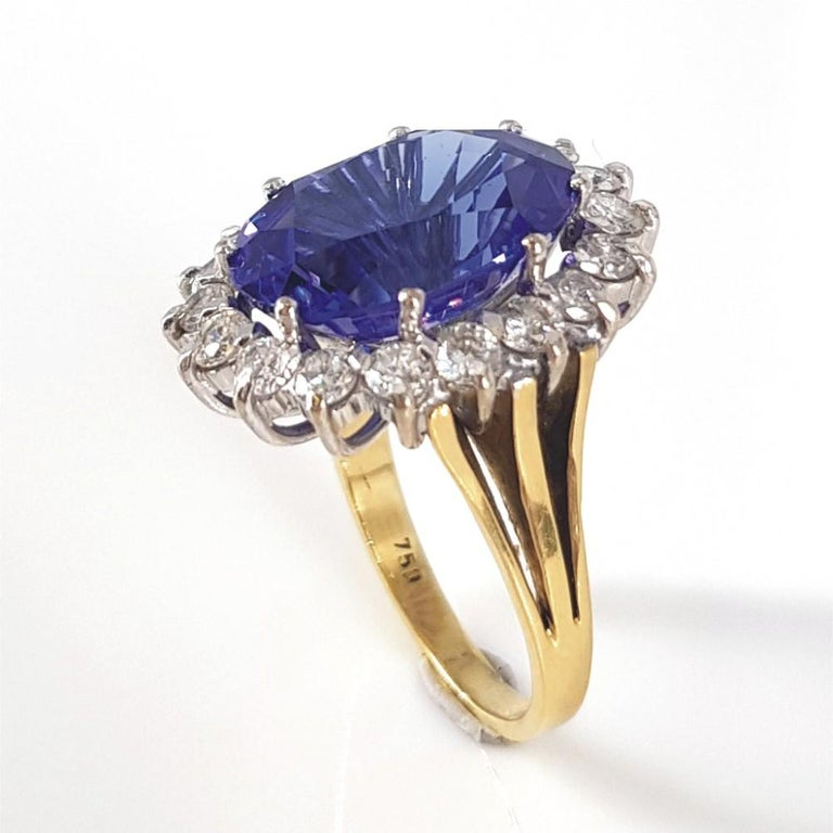 This beautiful piece giving us a Royalty feel is set in 18carat white & yellow gold weighing 8.5 grams. This Ring features 1 Oval Tanzanite weighing 8.16carat, and is surrounded 18 RBC Diamonds (IJ vssi) weighing 1.16carat in total. The ring size is