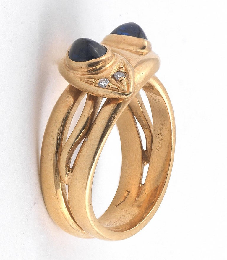 The mount modelled as two entwined snakes, each with a cabochon sapphire set in it's head and diamond eyes, finger size 7