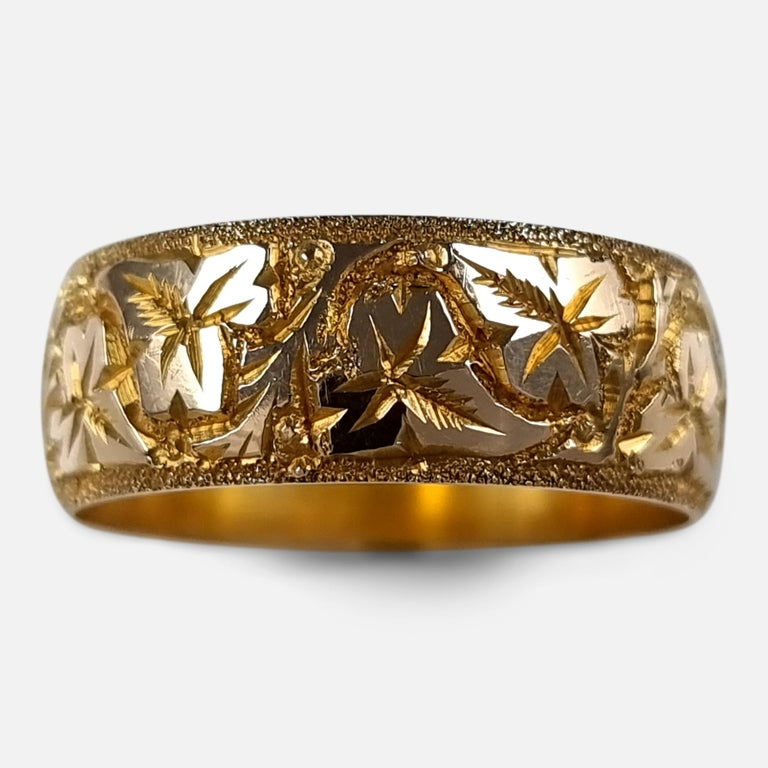 A George V 18ct yellow gold foliate engraved Keeper ring.  The ring is hallmarked with Birmingham marks, '18' for 18 carat gold, and date letter 'V' to denote 1920.  Assay: - .750 Gold (18ct).  Date: - 1920.  Period: - Early 20th