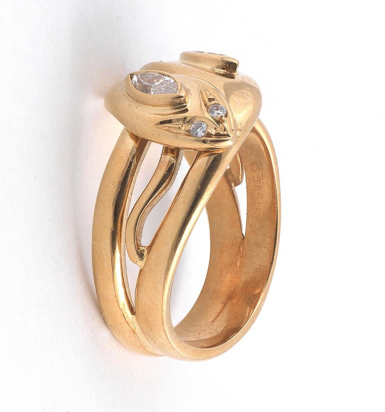the mount modelled as two entwined snakes, each with one white marquise brilliant-cut diamond and one brown marquise brilliant-cut diamond set in it's head, finger size 7 1/4