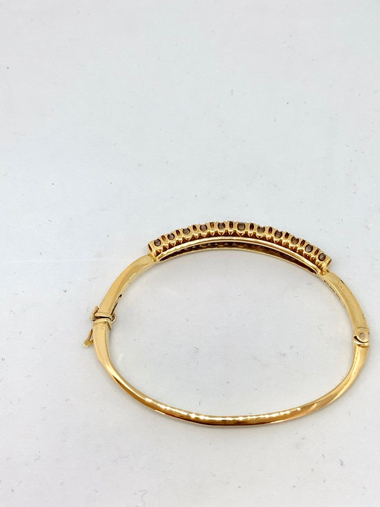 18ct yellow gold Victorian style hinged diamond set bangle. 1974 London assay mark J&P sponsor. Solid oval hinged bangle inside dimensions -60.0mm length x 46.0mm width Centre graduated claw set diamond section45.0mm length x 7.50mm width in the
