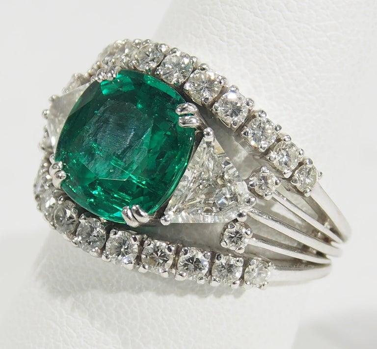 AGL Certified Emerald and Diamond Ring in 18K White Gold. The Center Stone is a Cushion Cut Emerald, approximately 4.0ct, enhanced with (2) Trillion Diamonds and (26) Round Brilliant Cut Diamonds weighing 2.15 carat total weight, G-H in Color, VS in