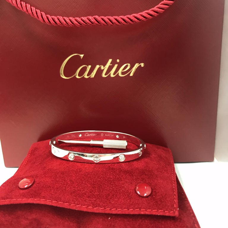 Cartier Love Bracelet in 18K White Gold.  (4) Round Brilliant Cut Diamonds weighing .42 carat total weight, F-G in color, VVS1 are bezel set in this classic Bangle.  Size 19.  35.45 grams.  Cartier Box, Gold Screwdriver and Cartier Certificate