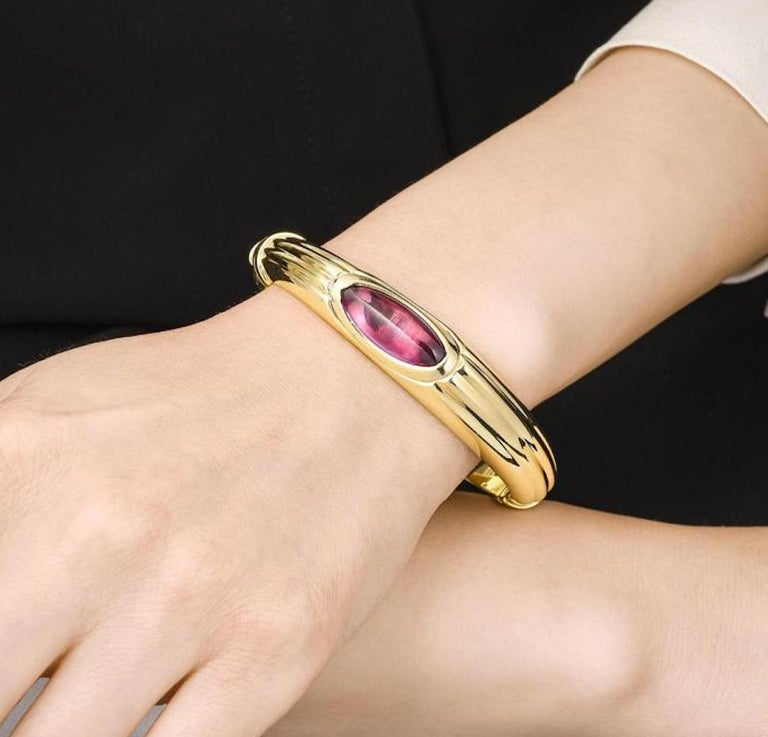 A lovely vintage bangle bracelet! The bangle contains an oval-cabochon amethyst, measuring approximately 22.45 x 8.65 mm, set in an 18K yellow gold bracelet with a hinged closure.  Stones: Amethyst  Metal: 18K Yellow Gold  Dimensions: 7