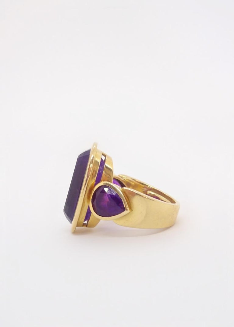 Mod cocktail ring in 18K yellow gold features a gorgeous step-cut amethyst with a royal purple color, flanked by two matched pear shaped amethysts all bezel set for a bold, chunky look.  Size 6