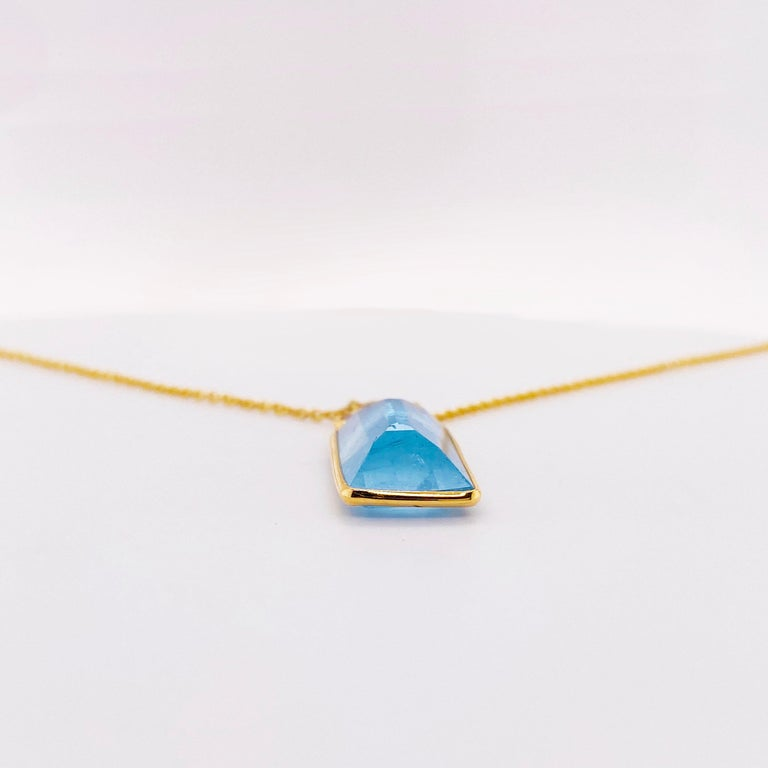 Lovely 6.05 carat emerald cut aquamarine set in an 18 karat yellow gold bezel affixed to a 1.00 millimeter 18 karat gold cable chain!  There are three bezels above the aqua that has three gorgeous .15 carat round diamonds in a triangle shape.  The