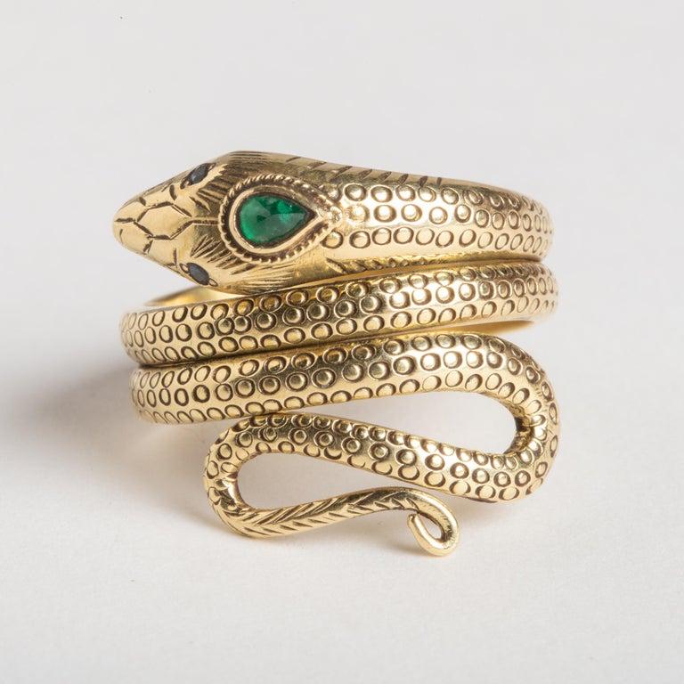 A finely hand-tooled coiled snake ring in 18K gold. Features a faceted, pear-shaped emerald third eye and faceted blue sapphire eyes.  The body of the ring has finely tooled scale details with a curled tail at the end.  Ring size is 7.5 with a bit