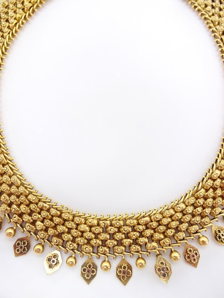 Each gold ball that connect to form the 5 rows in the body of this collar are decorated with a tiny florette of twisted wire. Entire collar rolls very nicely in your hand or with the body, and is accented by a row of alternating detail pendants;