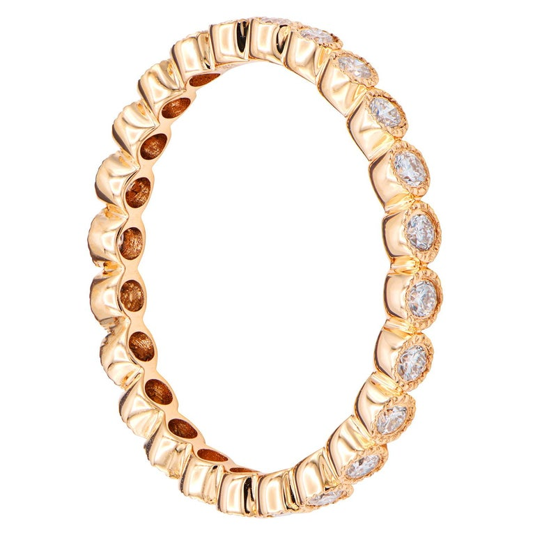 This stunning 18K rose gold eternity ring is made from 1.9 grams of gold. There are 23 round VS2, G color diamonds all the way around the ring totaling 0.44 carats. The gold around the diamonds has beautiful details to create this bezel setting.