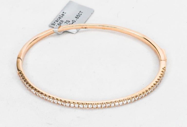 Rose Gold has a warmth that looks great on all skin tones.  Rich color!  This bangle bracelet has a clamper clasp that will click twice for security.  Top is a single row of beautifully matched white diamonds having a total weight of 0.85 carats.