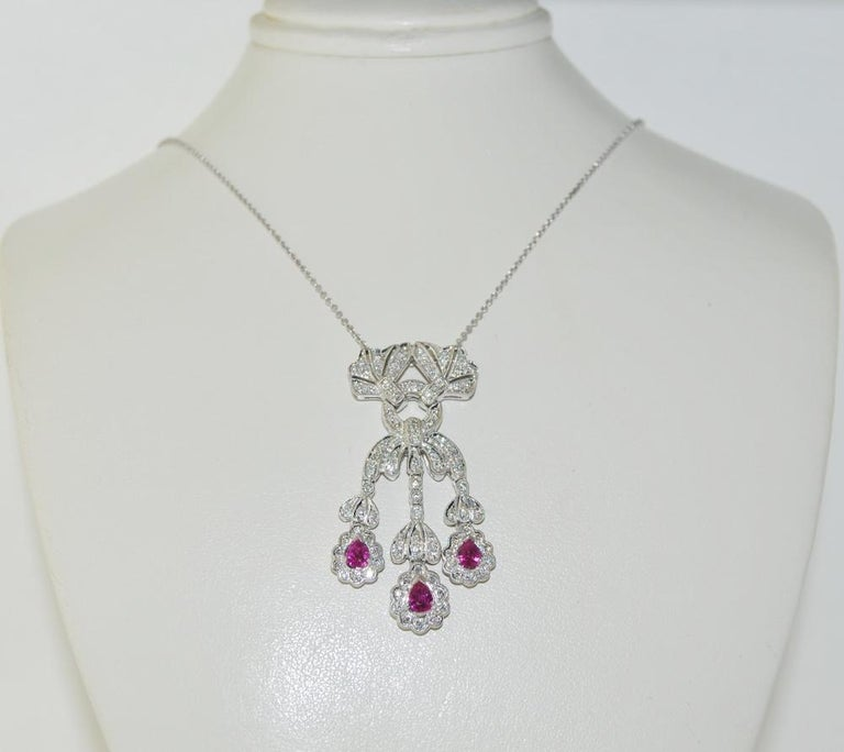 18K white gold pendant necklace featuring 0.85 carats of pear shape rubies and 0.50 carats of round diamonds and an 18 inches chain.