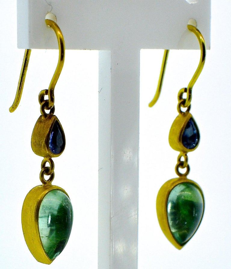 18K dangling earrings with 2 cabochon pear cut light blue sapphires weighing approximately .25 cts., and 2 cabochon cut light green emeralds weighing 2.5 cts.