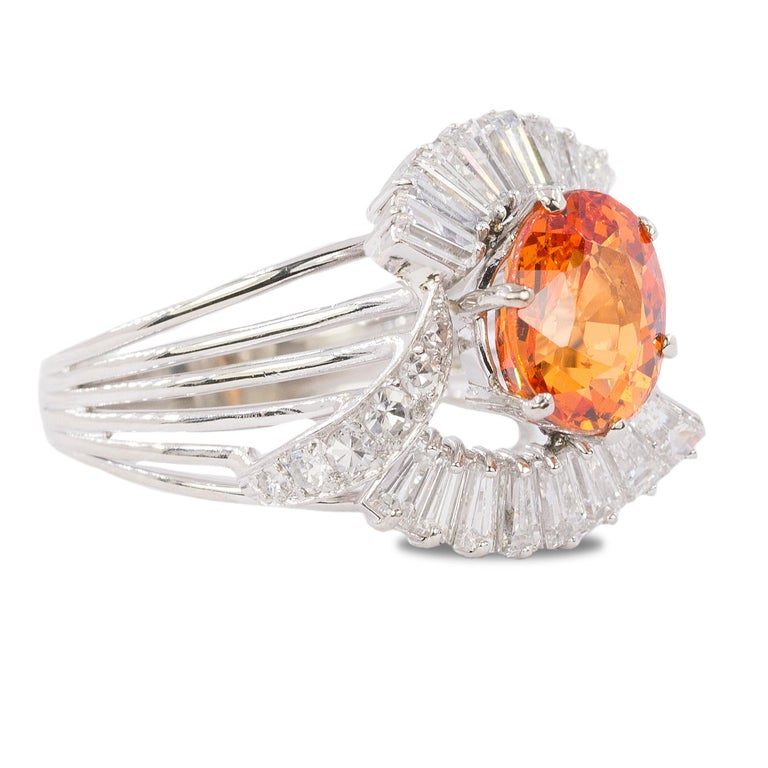 18k white gold ring with a 4.05 carat Spessartite Garnet and 16 tapered baguette and 12 round diamonds weighing approximately 1.30 carats.