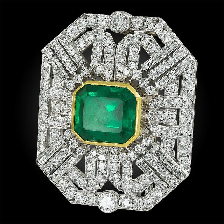 18k white and yellow gold brooch, set with round brilliant-cut diamonds total carat weight approx. 10.0 cts. and Colombian emerald weighing approx. 21 cts. with SSEF certificate. Dimensions approx. 2″ x 1 1/2″