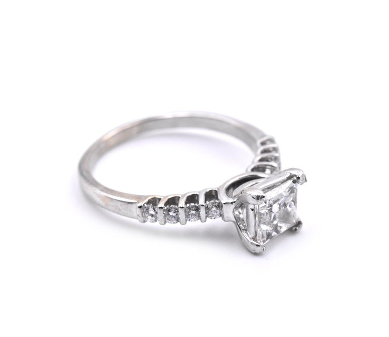 Designer: Custom Material: 18k white gold Center Diamond: 1 Princess cut = 1.10ct Color: F Clarity: SI2 EGS Certification: 011201131 Mounting Diamonds: 8 round brilliant cuts = 0.24cttw Color: F Clarity: VS - SI Ring Size: 7 (please allow two