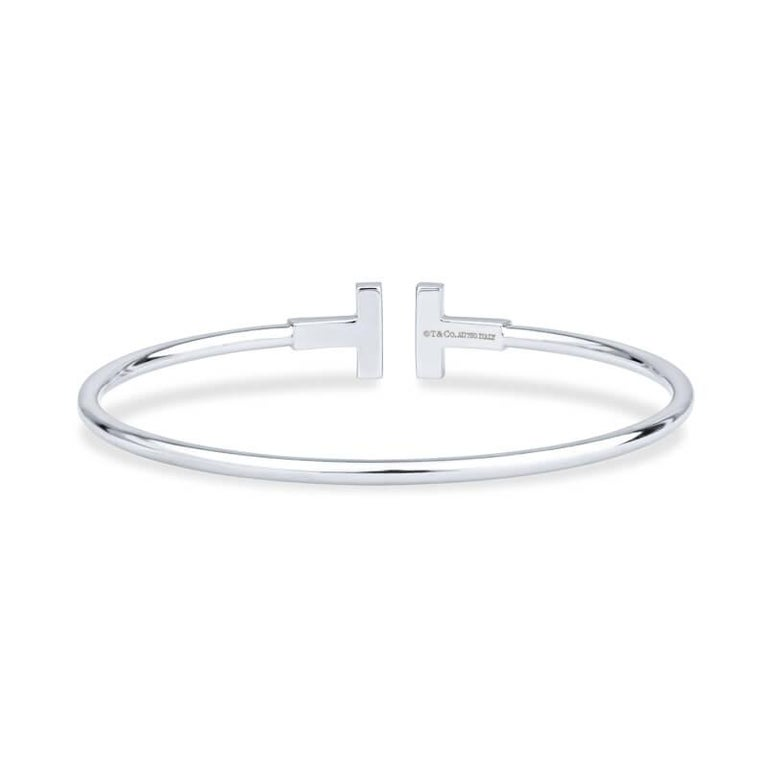 This bracelet from the Tiffany T collection is crafted of 18 karat white gold and features two horizontal T motifs adorned with 18 pave set rubies. Total carat weight is approximately .20 carats. This will fit up to a size 6.5 inch wrist.