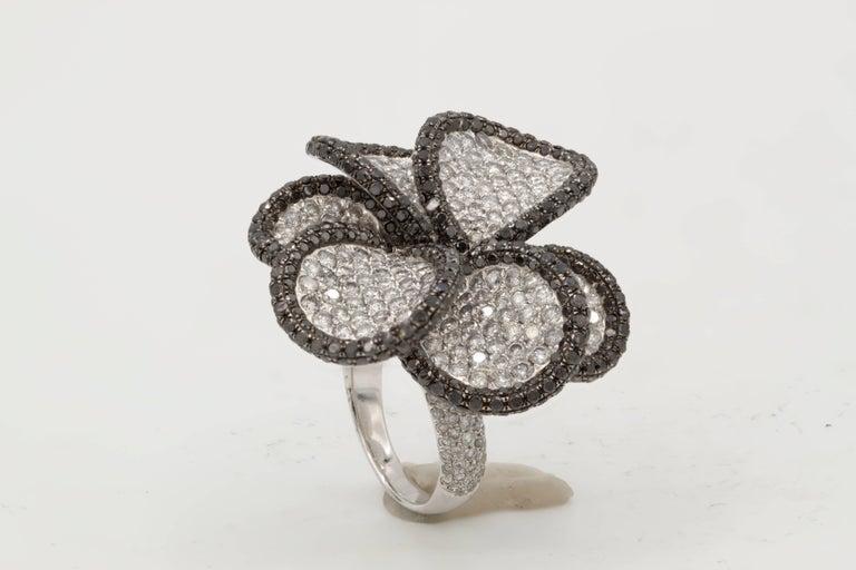 18K White Gold Black and White Diamond Flower Ring, features 6.80 carats of Black and White Diamonds.