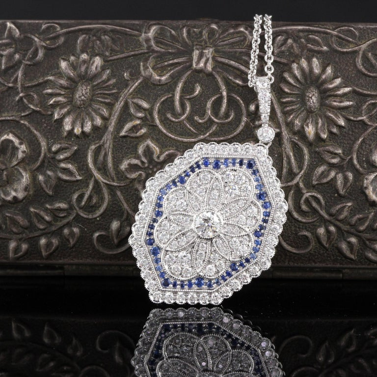 Gorgeous sapphire and diamond pendant with dazzling diamond center.  Metal: 18K White Gold  Weight: 8.1 Grams  Diamond Weight: Approximately 1.20 ct.  Diamond Color: G  Diamond Clarity: VS2  Gemstone Weight: Approximately 0.50 ct.