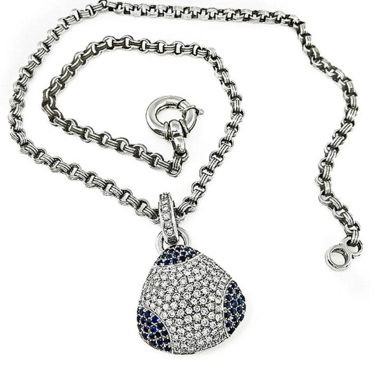 This fabulous 18k white gold pendant is set with sparkling round cut diamonds that weigh approximately 3.00ct. graded G-H color with VS clarity. The diamonds are accentuated by lovely round cut sapphires that weigh approximately 1.50ct. The pendant