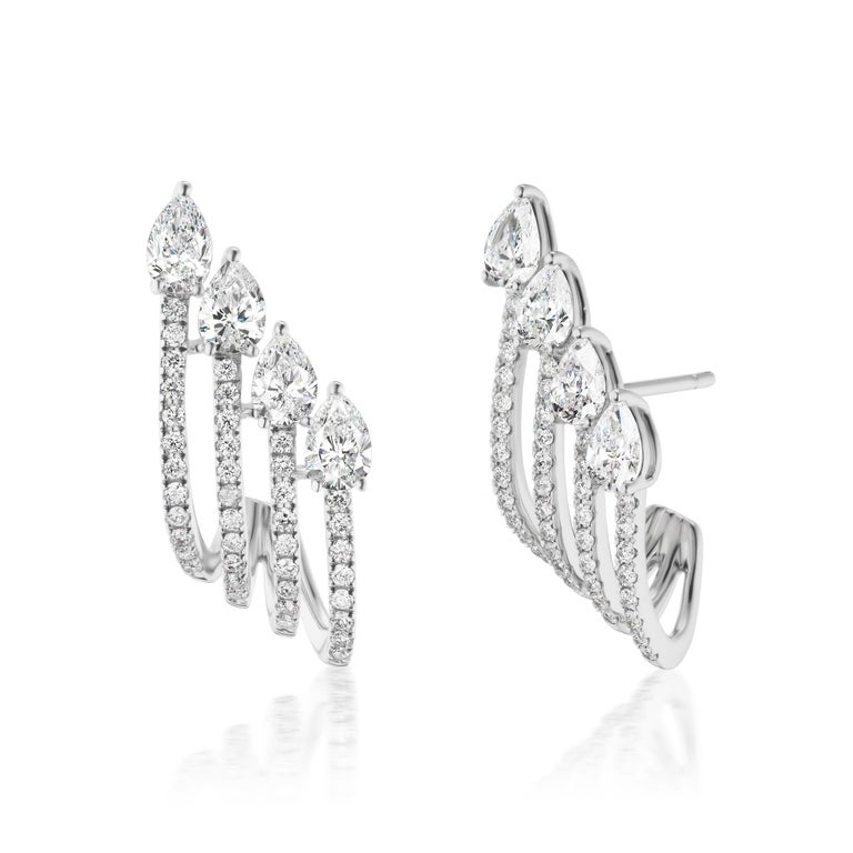 Studs can be a great option especially when it comes to contemporary styling. This pair is made in 18k white gold and is studded with beautiful white pear shape diamonds  and round pave set diamonds. The multitier arrangement of the stones enhances