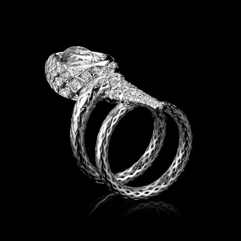 Modern, designer cocktail ring in 18K white gold set with diamonds with intricate details. A serpent coils around the wearer's finger, stretching towards the light of the torch depicted by a large pear shaped diamond and surrounded by a pave of