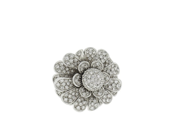 This ring features 3 carats of G VS pave diamonds set in 18K white gold. This intricate cocktail ring has unique floral petals that move mimicking a life like flower petal with each movement of the hand. Total weight 25 grams. Made in Italy. Size
