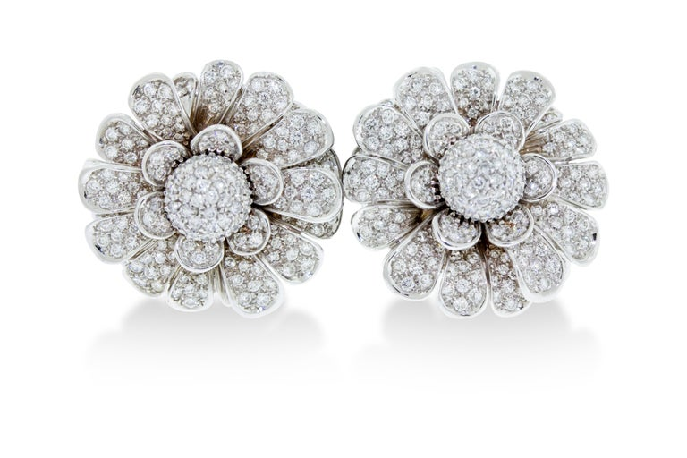 A pair of pave diamond ear clips featuring petals that move mimicking a life like flower. Made in Italy. Set in 44 grams of 18K white gold with a total diamond weight 6 carats. 1.25 inch diameter.  Viewings available in our NYC showroom by