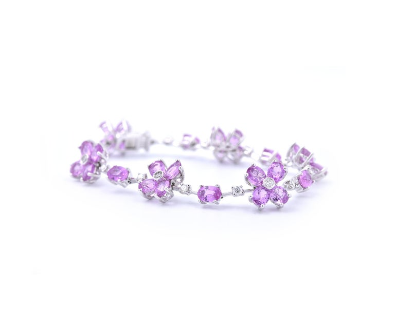 Designer: custom design Material: 18k white gold Sapphires: 30 oval cut pink sapphires Diamonds: 18 round brilliant cuts = 0.66cttw Color: G Clarity: VS Dimensions: bracelet will fit up to a 6.5-inch wrist and measures 11.2mm in width Weight: 15.25