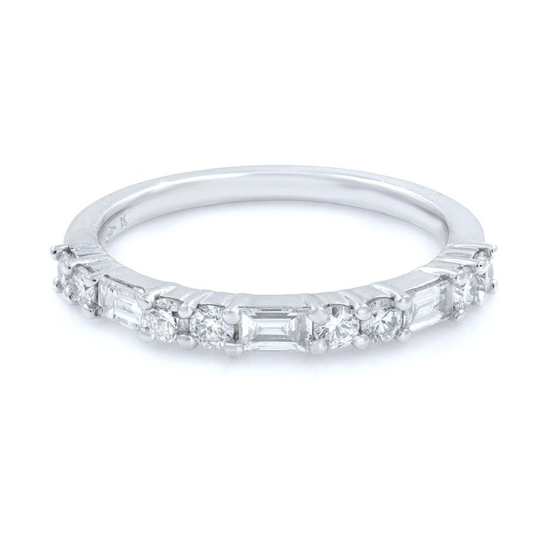 Alternating sections of two round brilliant cut diamonds and one baguette cut diamond continuing half way around in a 18 karat white gold prong setting wedding band.  Carat weight: 0.58cts Size: 7