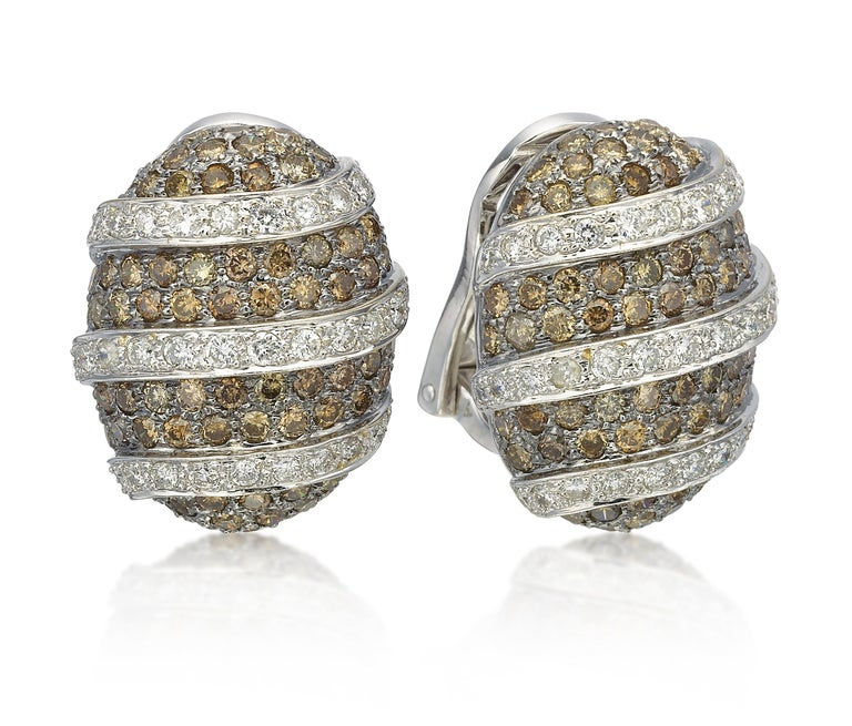 Exclusively from our estate collection, come a delicious brown and white diamond fashion earrings that are a delight. The omega back earrings are set in 18K white gold in a hypnotizing pave of 152 brown diamonds (3.00 ctw, SI clarity) and 70 white