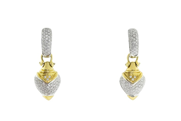 These earrings set in 18K yellow and white gold feature a diamond pave huggie hoop earring with a removable heart charm. 5.04 carats of pave G-H VS diamonds and 17g of 18K yellow and white gold. Made in Italy.    Viewings available in our NYC