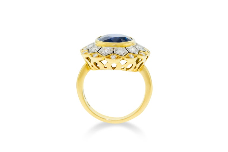 This ring features a 7.0 carat oval cut blue sapphire stone 18K yellow and white gold surrounded by 24 G-H VVS-VS round diamonds weighing 0.75 carats. Includes Gemological Appraisal Laboratory of America Certificate. 10.8 grams total weight. Made in