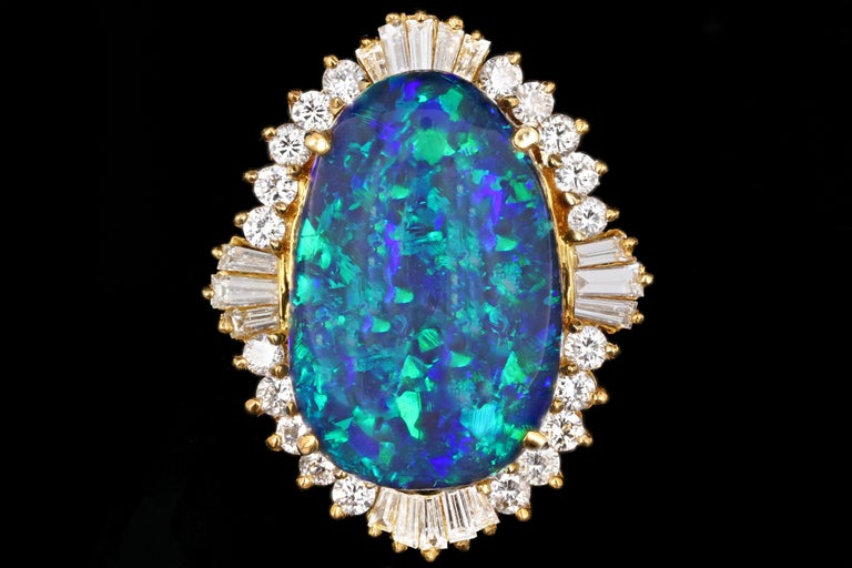 Era: Modern  Composition: 18K Yellow Gold  Primary Stone: Black Opal  Carat Weight: 20 Carats  Accent Stone: Baguette and Round Brilliant Cut Diamonds  Carat Weight: 2 Carats  Color: F-G  Clarity: Vs1/2  Total Carat Weight: 22 Carats  Ring Weight: