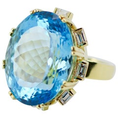 18 Karat Gold 66 Carat Oval Blue Topaz with a Halo of Emerald Cut Diamond Ring