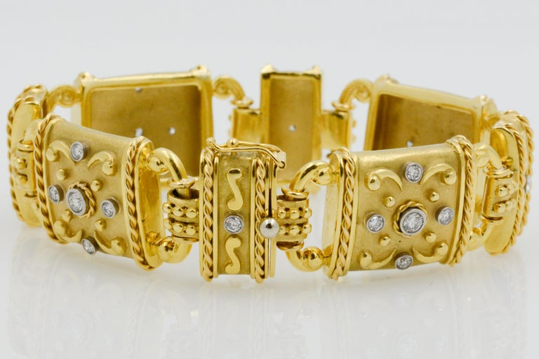 24 round dazzling diamonds with a combined weight of 1.50 carats are accented with 18k yellow gold scroll work. The flexible bracelet is separated by eight linked panels to create a charming and elegant design.