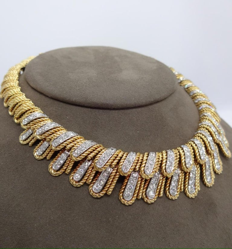 Over 10 carats (approximately 10.85) of round brilliant diamonds are set in platinum and 18K yellow gold layered, twisted wire feathered motif this stylish diamond necklace.  While it currently measures 13.75inches, it can easily be lengthened for