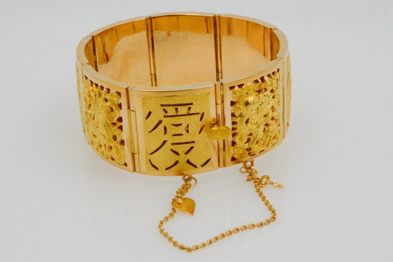 This 18k yellow gold Asian bracelet features four season design panels among the total eight panels. The bracelet is wide, measuring at 25mm.