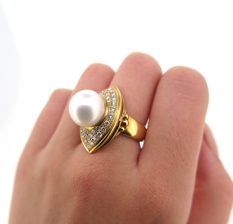 Featuring an 18 Karat yellow gold modern dress ring with a marquise shaped top plate. The ring is set with a 11.8 mm uniform round cultured south sea pearl. the peal is surrounded by 38 graduated modern Round Brilliant Cut Diamonds. The ring has a