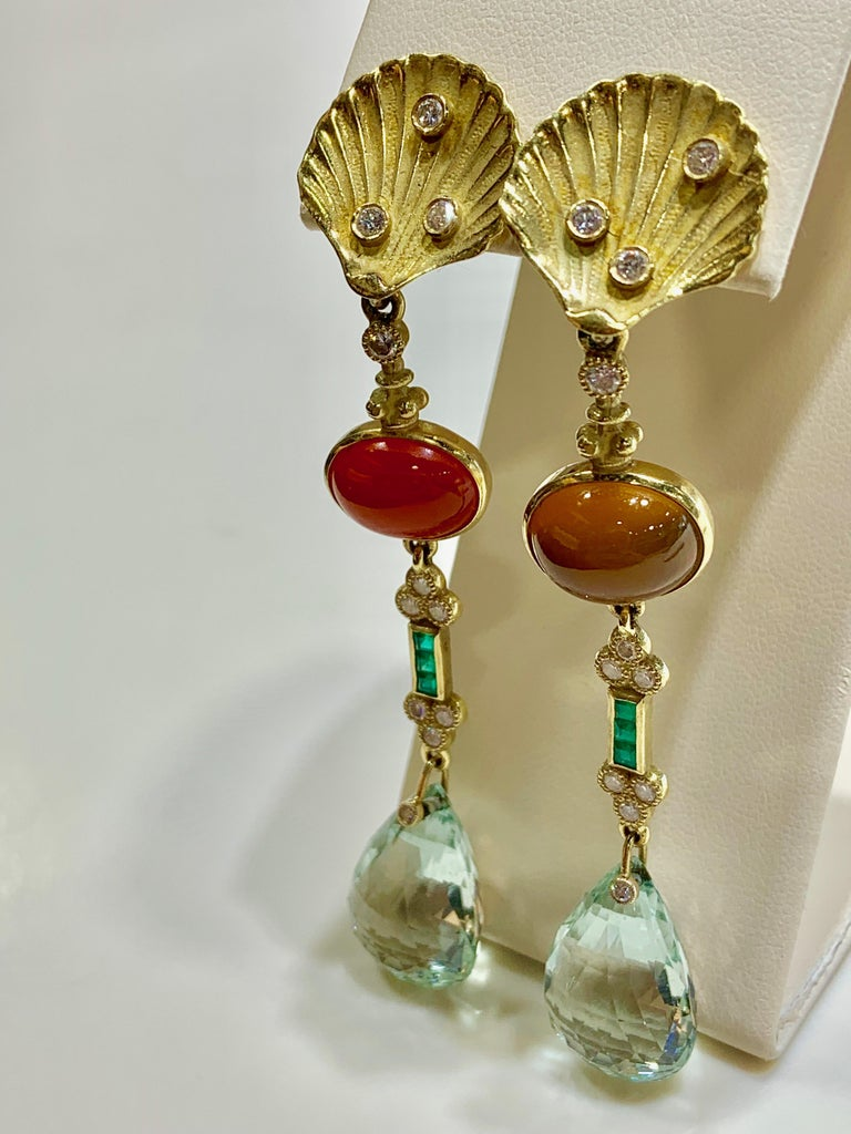 Beautiful 18K yellow gold multi station seashell drop earrings created by award winning designer, Yves Kamioner. Each earring features round bezel set diamonds, princess cut emeralds, and a 20mm by 14mm briolette cut Aquamarine. One earring holds a