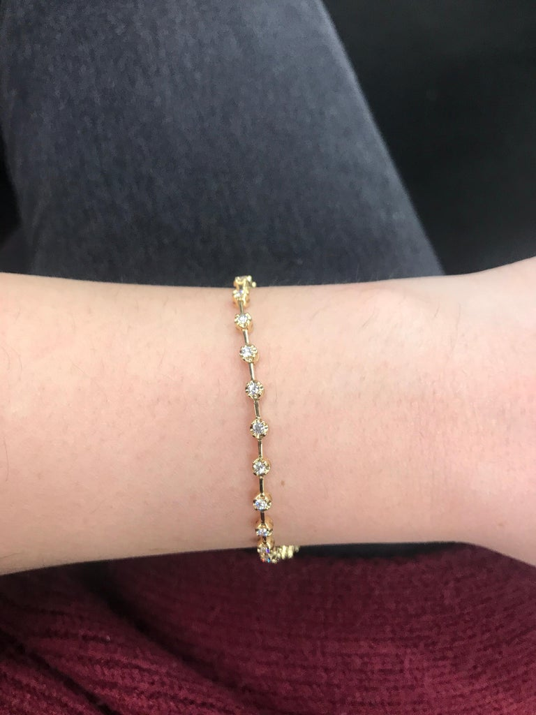 18K Yellow gold tennis bracelet featuring 30 round brilliants in a yellow gold floral bezel weighing 0.91 carats. Color G-H Clarity SI