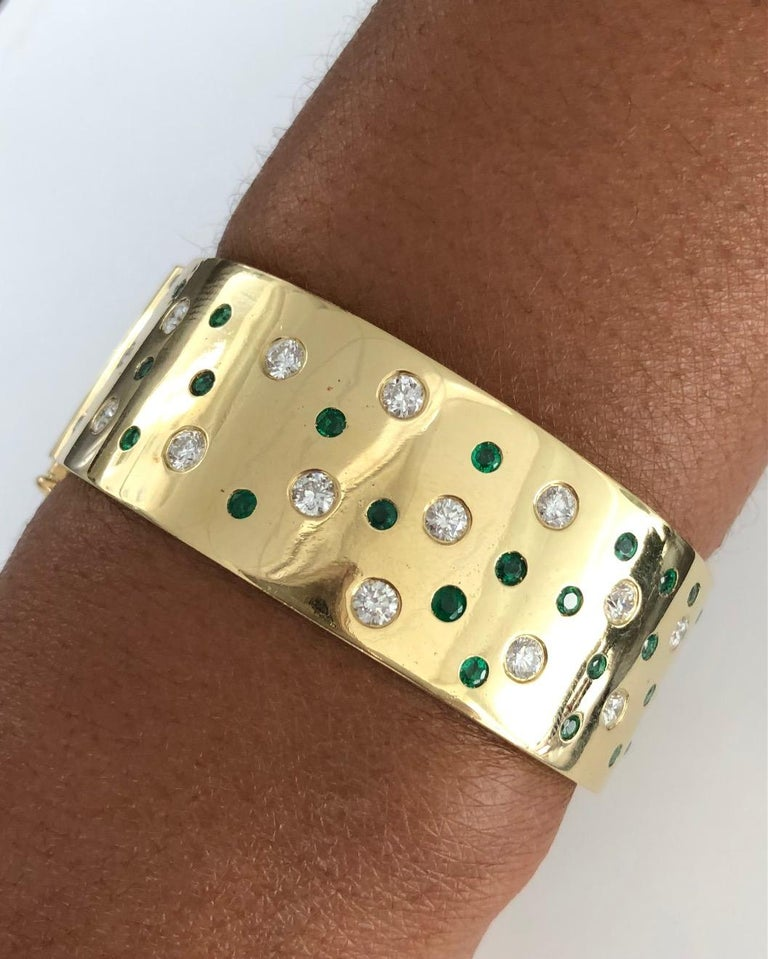 Fashionable wide Bangle Bracelet, made in 18K Yellow Gold, set with a combination of Diamonds( 2.61 carats ) and Emeralds ( 1.60 carats ), featuring our easy push-button opener. Bracelet width: 7/7 inch ( 2.3 CM )  We design and manufacture our