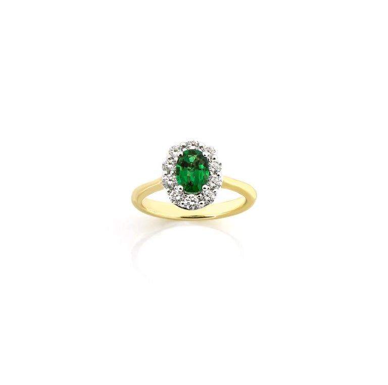 A princess-perfect look and a thoughtful gift for the birthday girl born in May! Fashioned in elegant 18K yellow and white gold, this ring features a remarkable 0.80ctw oval-shaped emerald gemstone with ten sparkling 0.57ctw (G-H color and VS