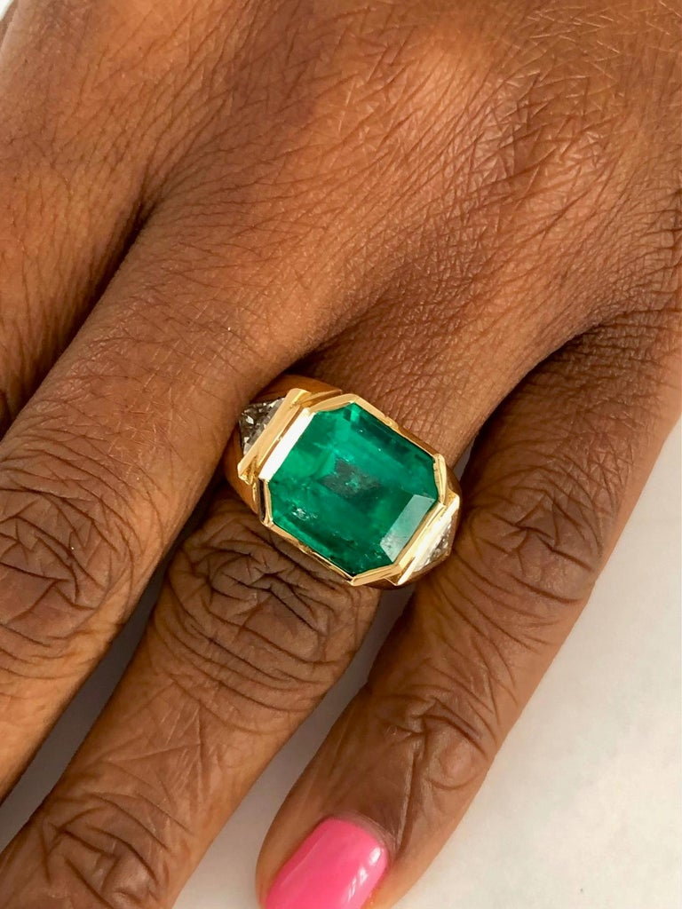 This one of a kind, handmade 18K Yellow Gold ring, set with a Colombian Emerald 8.41 carats and two Diamonds 0.93 carats. Styled to look different than the cookie cutter look....  We design and manufacture our jewelry in our workshop, located in New